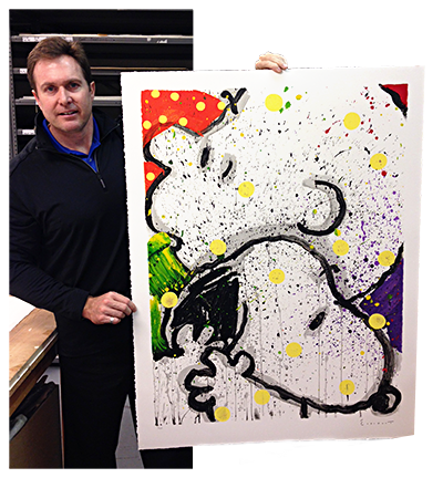 Tom Doyle at the Rue Royale Warehouse holding up a Peanuts, Snoopy lithograph